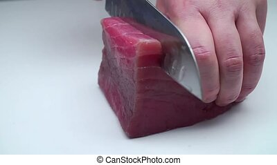 The cook cuts a piece of jerky with a knife. A man's hand...