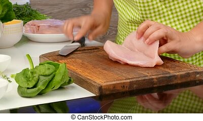 The cook cuts the chicken breast and makes her stuffing -...