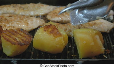 The cook fries potatoes and turkey fillets on the grill. Very tasty and mouth-watering. Close-up.