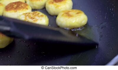 The cook fries small cutlets in a frying pan