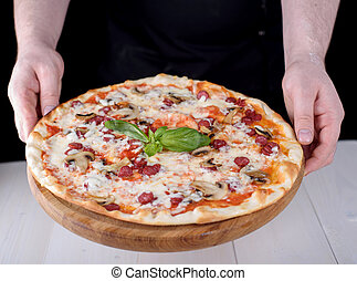 The cook is holding pizza with salami on a wooden board