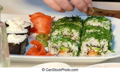 The cook makes a beautiful sushi dish - Hands lay out...