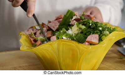 The cook mixes vegetables and ham salad in beautiful ware -...