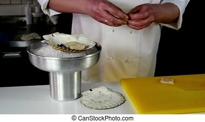 The cook prepares a sea salad of scallops.