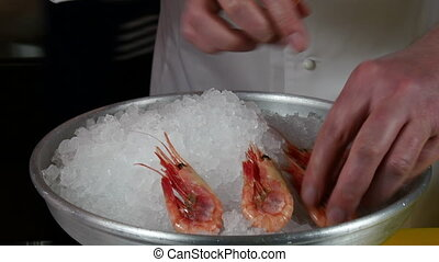 The cook prepares dish of boiled shrimp on ice.