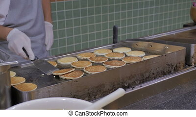 The cook prepares pancakes in the hotel restaurant for breakfast.
