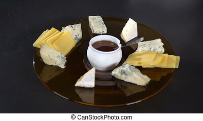 The cook puts the pieces of cheese on a plate of honey