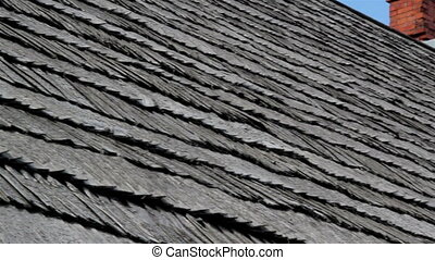 The corner of old cedar wooden shingle shake roof of the house and a clean chimney water tin
