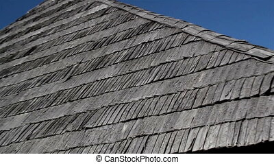 The corner of old cedar wooden shingle shake roof of the house Zoomed image