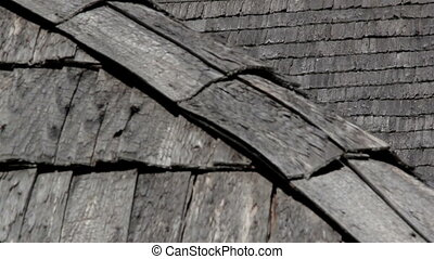 The corner of old cedar wooden shingle shake roof of the house