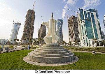 The Dallah coffee pot sculpture on the Corniche in Doha the capital of Qatar, behind it are the new high rise building being built to fill the skyline.