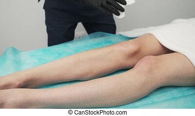 The cosmetologist wipes the remnants of the gel on the client after the procedure of laser hair removal.