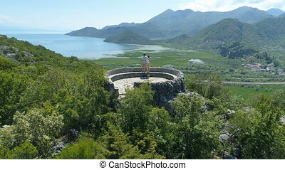 the couple embraces each other and enjoys a magnificent view from the observation deck of Lake Skadar