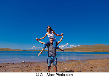 the couple is near the water near the river. a man and woman plays by the pond. a woman rides on a man's neck