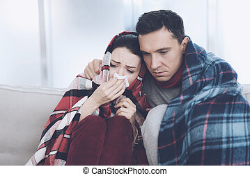 The couple is sitting on the couch wrapped in blankets. Man and woman are sick. A man hugs a woman who flies