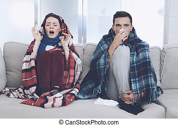 The couple is sitting on the couch wrapped in blankets. Man and woman are sick. The man flies out. Woman sneezing