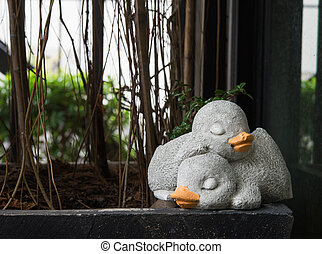 The couple of sleeping duck made from cement for decoration