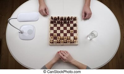 The couple plays chess. The woman loses the game and throws figures. Top view. Hands close up view