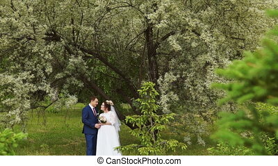 The couple stand in front of the tree