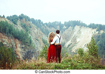 the couple stands in the mountains