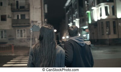 The couple walks from the camera at night crossing the road...