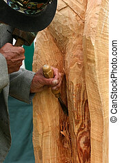 The Craftsman at Work - Wood carver with a chisel, carving a...
