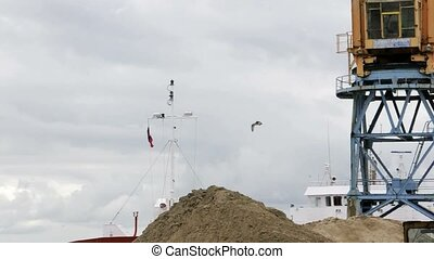 crane dredge of a ship unloads sand - The crane dredge of a...
