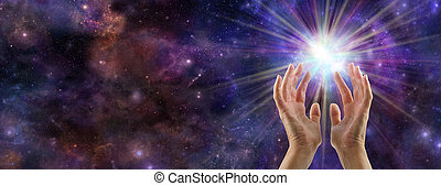 Female hands reaching up to a white burst of light on a wide deep space background with plenty of copy space on left hand side