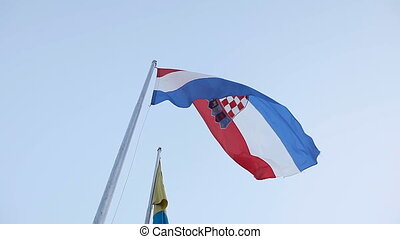 The Croatian flag flies against the background of a blue sky...