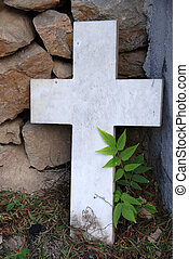 A white marble cross leaning on a rocky wall