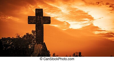 Silhouette of a cross against a red sky background.