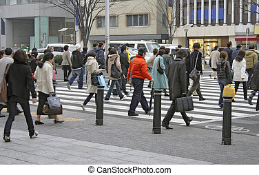 Image of people crossing the street in a downtown area.