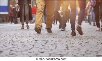 The crowd of tourists walking on a cobblestone