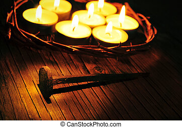 the crown of thorns on the holy cross and some lit candles, with