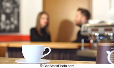 The cup of coffee on the background of the couple in the...
