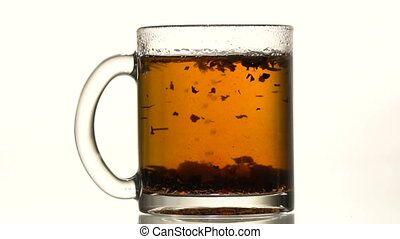 The cup of tea thrown refined sugar - A glass cup of black...