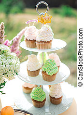 the cupcakes are beautiful and colorful on the table outdoors