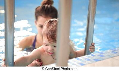 The cute baby getting out from the swimming pool