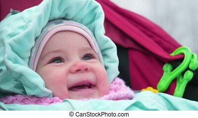 The cute little baby in the pram smiling. - The cute child...