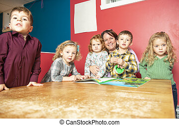 The cute preschoolers group in kindergarten together read a book
