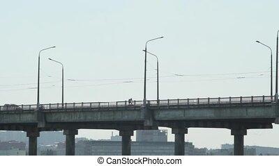 The cyclist rides across the bridge
