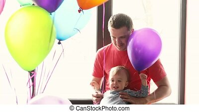 The daddy with the baby boy look at a balloon - Father with...
