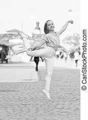 The dancer is at her best. Adorable street dancer. Little female dancer performing ballet leap on street. Small cute girl dancer dancing on summer day