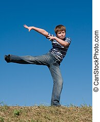 The dancing little boy against the blue sky