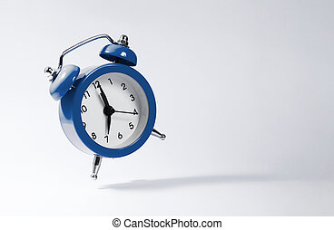 The dark blue alarm clock bounces against the background.