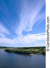 The dark blue sky with clouds over river