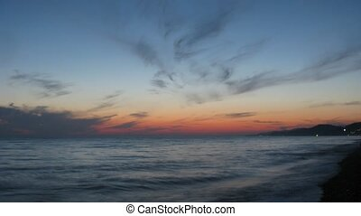 The dark sunset sky over the sea, sea surf.