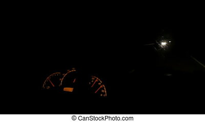 The dashboard of a moving car with sparkling lamps at night.
