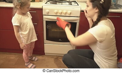 The daughter and her mother get out of the oven pizza