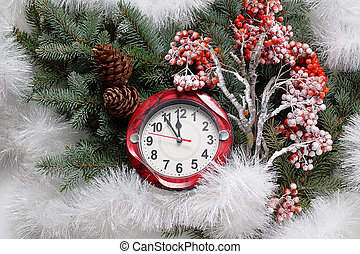 The decoration of Christmas party. Snow-covered branches of mountain ash, Christmas balls and clocks.